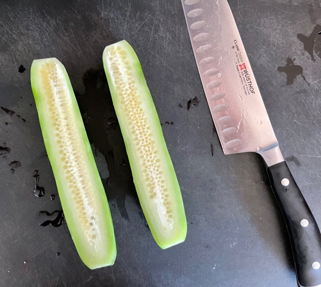 A cutting board with a knife and a cucumber sliced in half