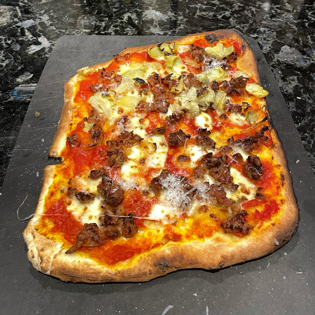 a funny shaped and slightly burnt pizza with sausage, fennel, and artichoke hearts