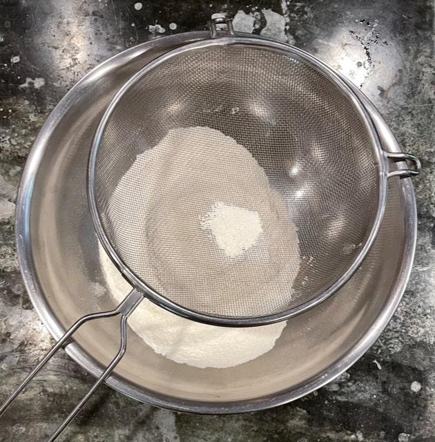 a sieve over a bowl of flour