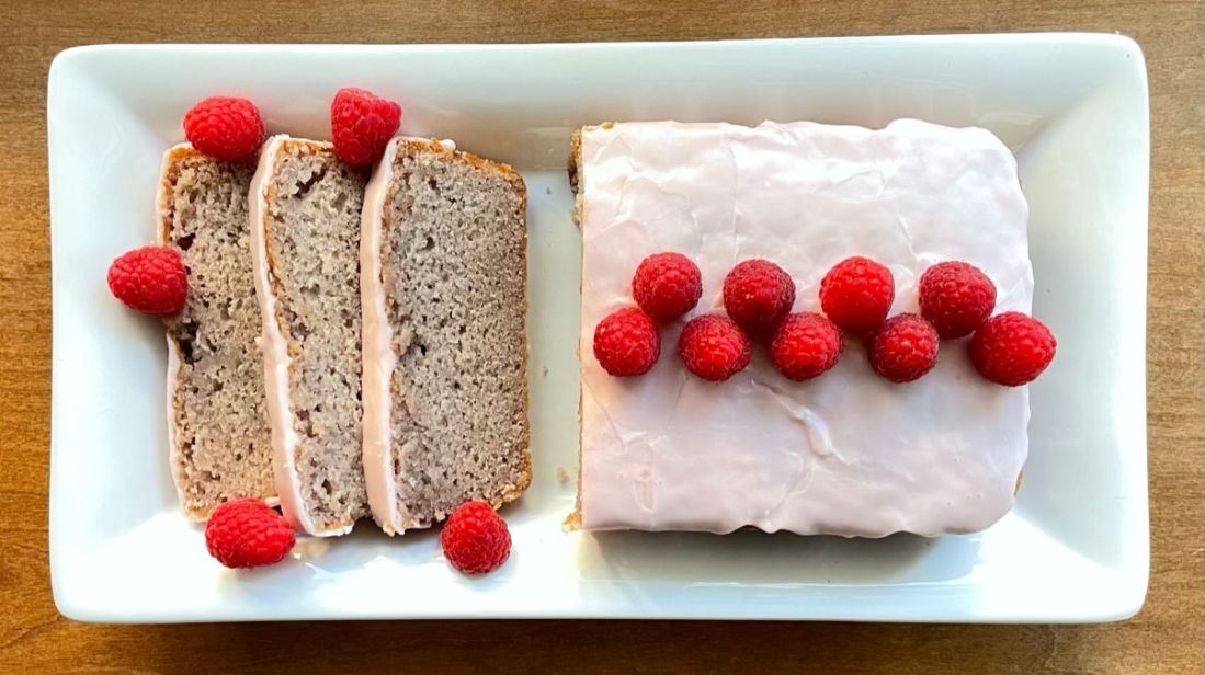 the summer raspberry cake on a white plate cut into a few slices and decorated with fresh raspberries