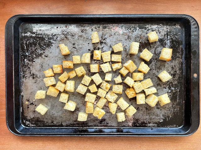 A baking sheet filled with sourdough croutons