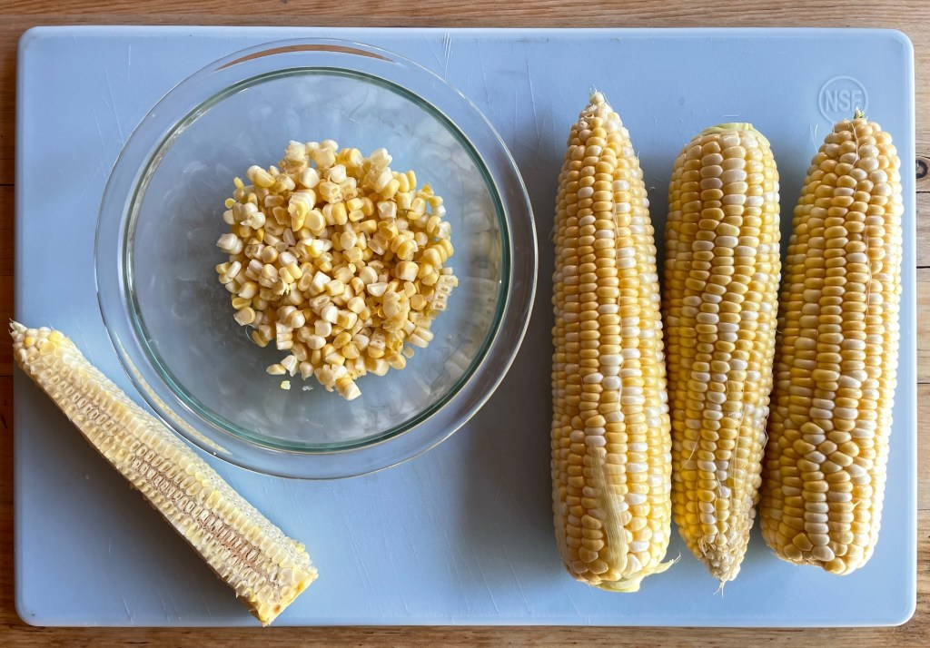 a cutting board with three ears of corn, a corn cob, and bowl of corn kernels