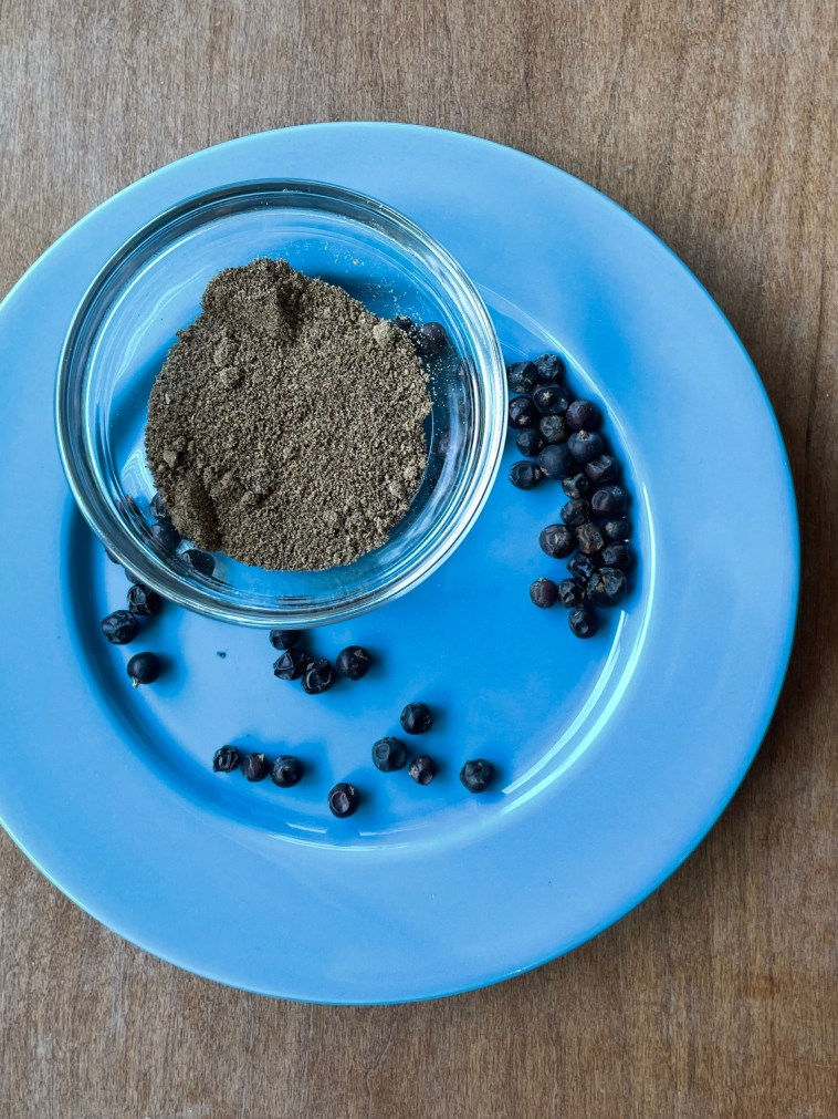 a plate containing dried juniper berries and a glass bowl of ground juniper
