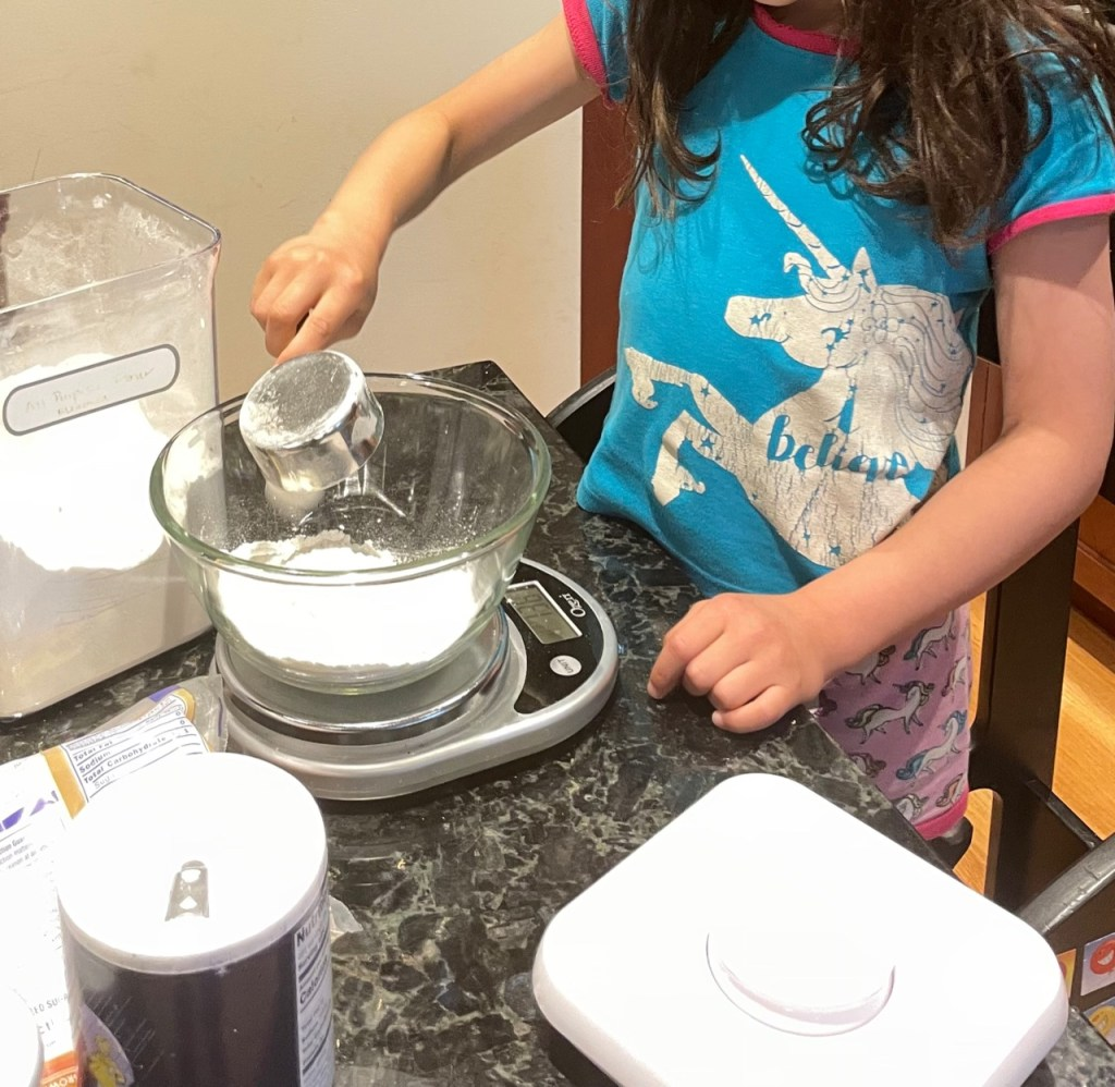 a young child scooping and weighing out flour