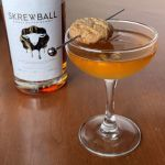 a bottle of Skrewball peanut butter whiskey and a brown cocktail garnished with a peanut butter cookie