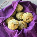 a basket filled with spinach and feta muffins and lined with a purple napkin