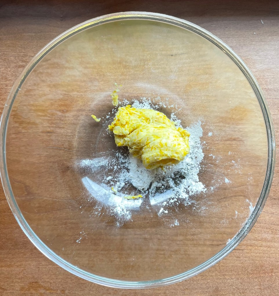 a bowl containing flour, salt, and spices, and the squeezed ball of grated squash