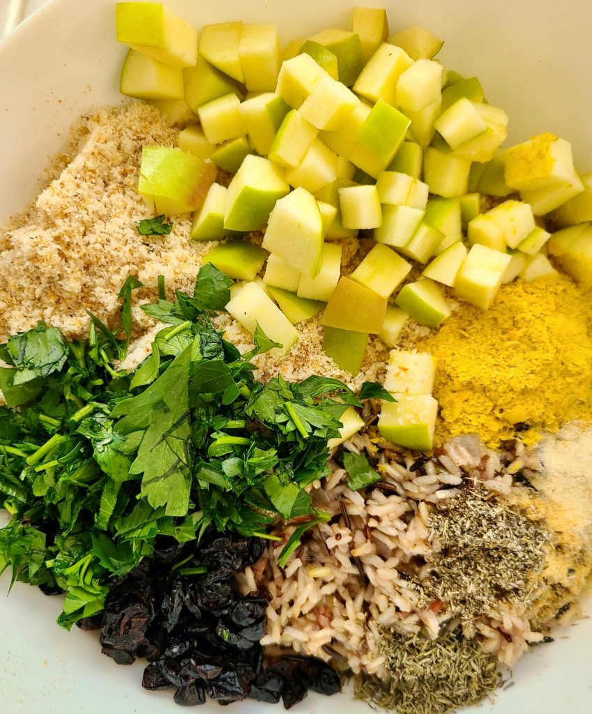 Green apples, nutritional yeast, wild rice blend, dried cranberries, parsley, bread crumbs, and dried herbs in a mixing bowl