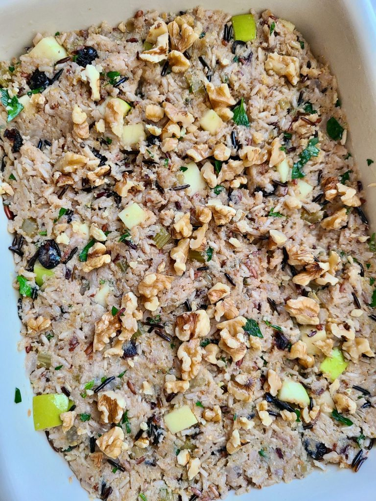 Spreading the cranberry apple stuffing into a dish, and topping with walnuts