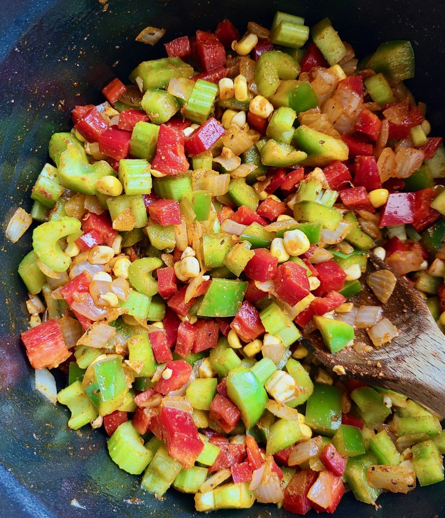 Green peppers, red peppers, sweet corn, celery, onions, garlic, cajun seasoning, smoked paprika, and bay leaves in a pot