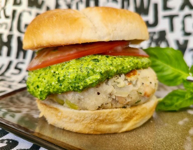 Vegan white bean veggie burger with tomato slices and vegan pesto