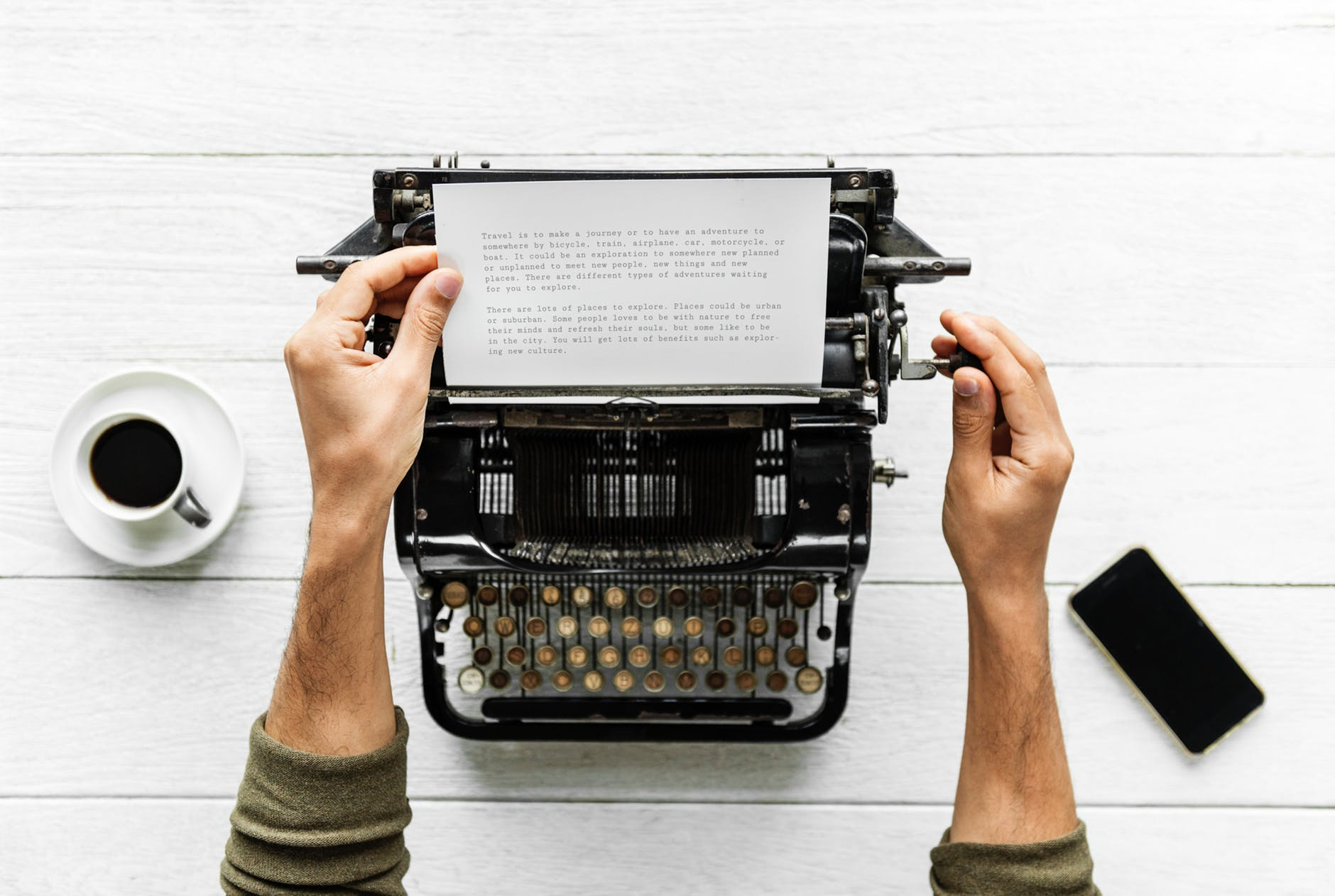 person holding white paper and typewriter