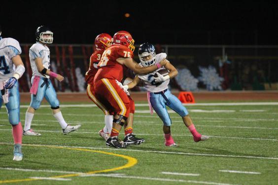 Matt Abellaneda (#21) holds off a WHS defender after receiving a pass from quarterback Wes Jordan (#7) (Lexi Lim)