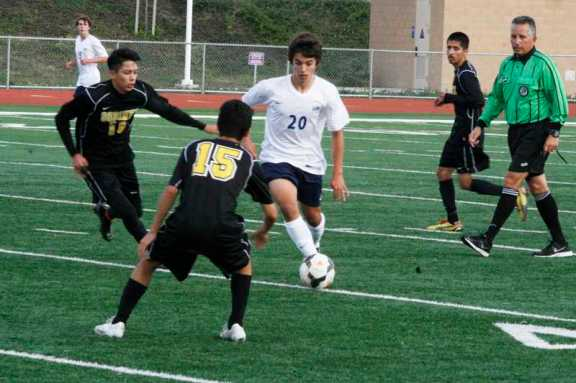 Marcos Fernandez (#20) maneuvers between Godinez defenders. (Ken Nguyen)
