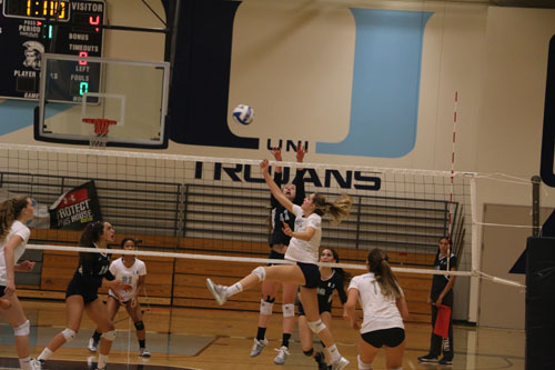 Captain Bella Oldham (Sr.) blocks the ball early in the second set against CdM. (M.Olney)