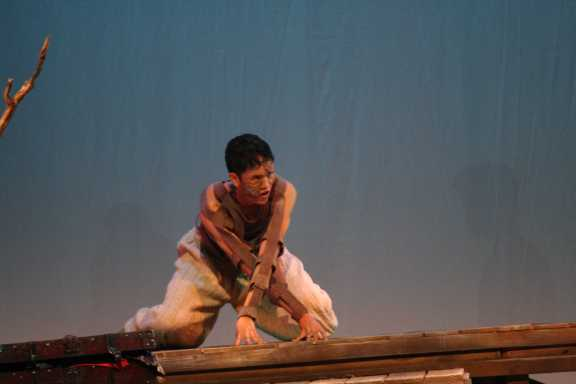 Caliban, played by Dalton Nguyen (Sr.), emerges from his prison.
