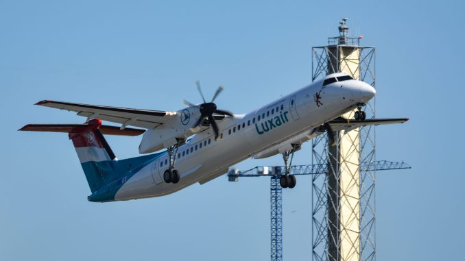 A Dash 8 climbs out from London City Airport past the new digital control tower mast