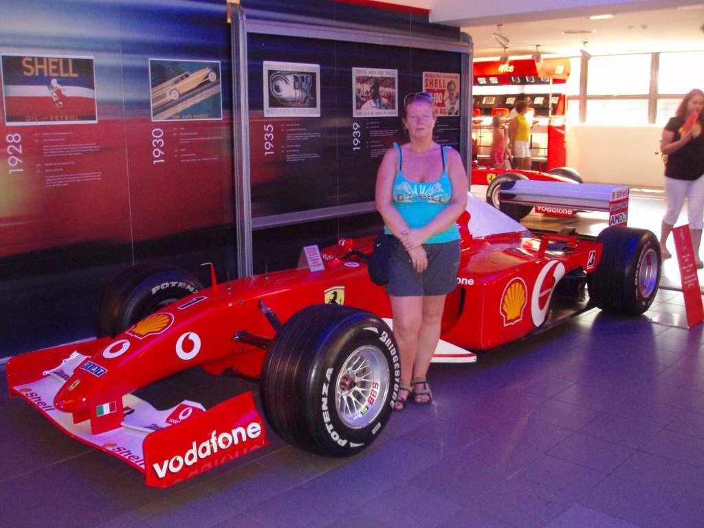 a lady stood by a Ferrari F1 car at Modena