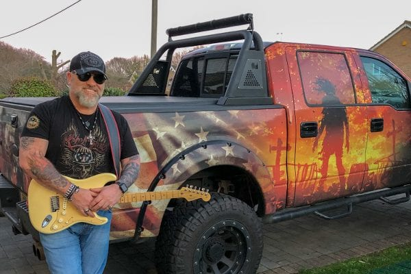 Bobby with a guitar leaning against a truck