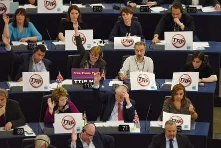 Members of 'Europe of Freedom and Direct Democracy Group' sit behind posters on their desks which read 'stop TTIP', during a voting session at the European Parliament in Strasbourg, France, 07 July 2015. The European Parliament will vote on 08 July on the EU-US Transatlantic Trade and Investment Partnership (TTIP).