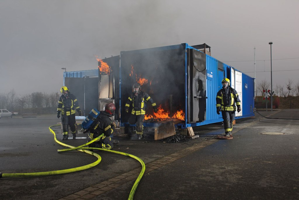 Hot fire training with Dräger FTS 8000 mobile fire training facility and firefighters using Dräger firefighting equipment.