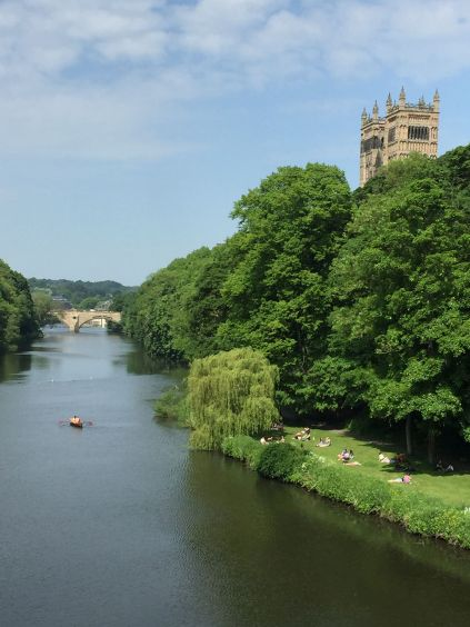 Twin towers of the west front of Durham Cathedral rise above the River Wear in Durham, England