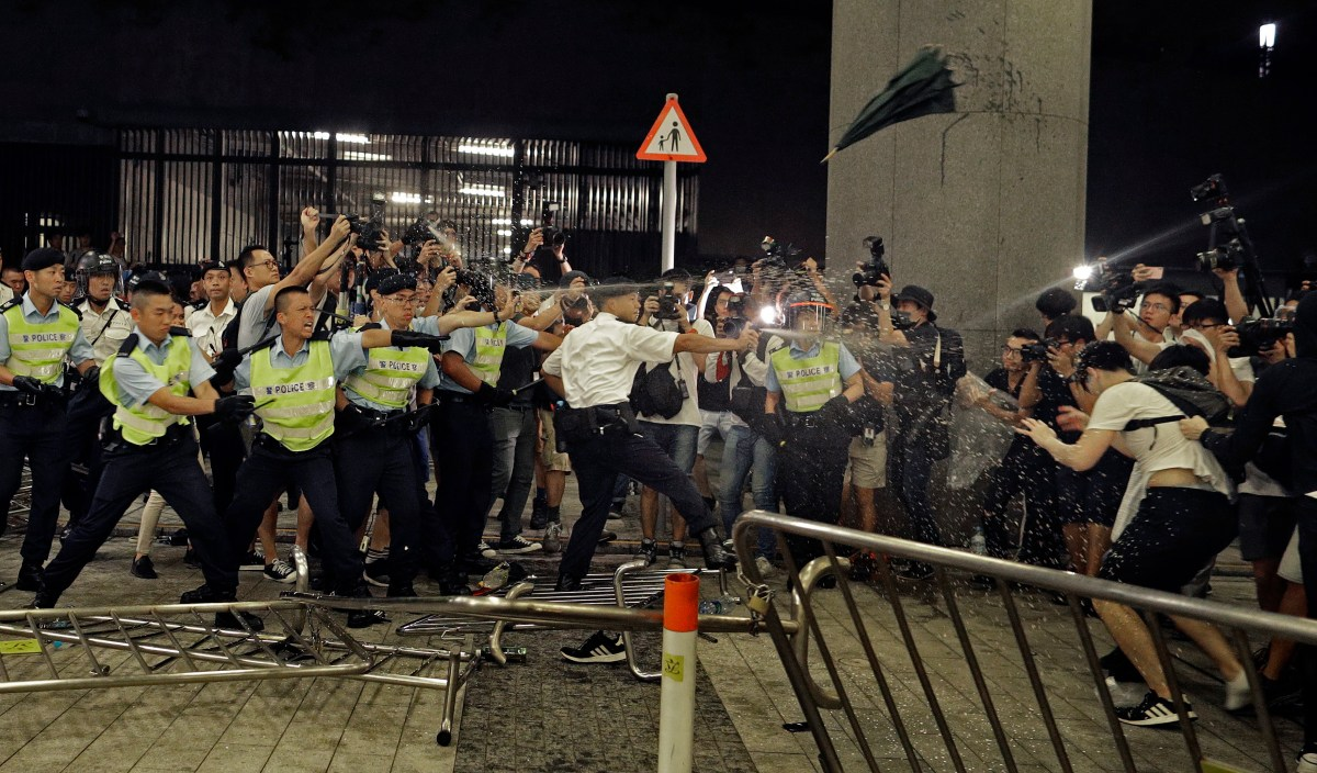 Police officers use pepper spray during a rally against a proposed extradition law at the Legislative Council in Hong Kong.
