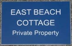 A small engraved house sign in blue acrylic laminate