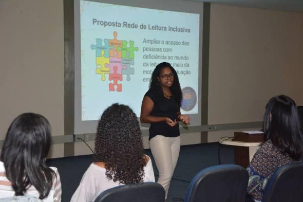 mulher dando palestra com o slide sobre proposta rede de leitura inclusiva