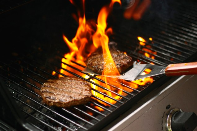 A burger being grilled on a barbecue, with flames