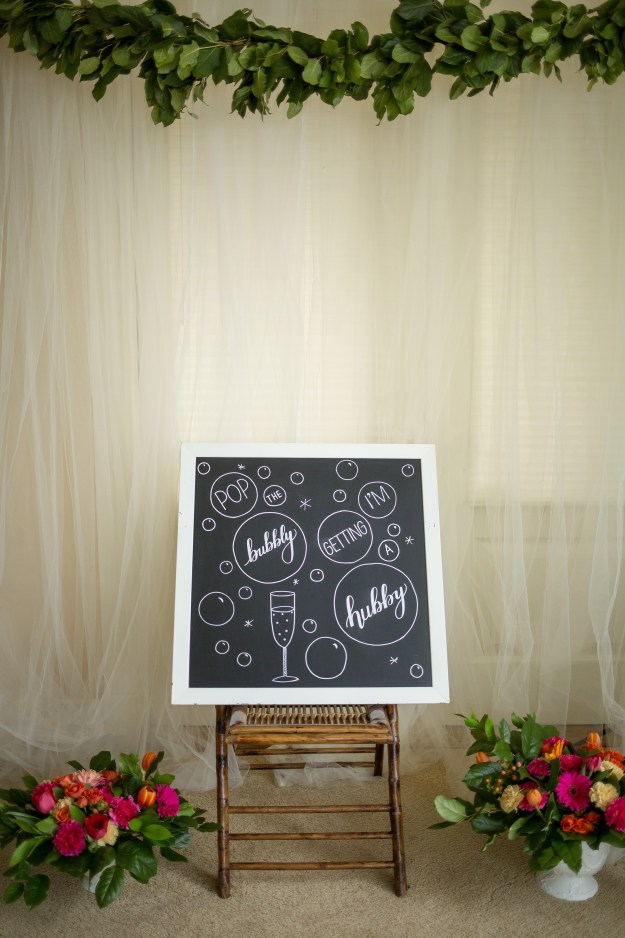 This cute chalkboard sign welcomed guests to a champagne bridal shower with the message Pop the Bubbly, I'm Getting a Hubby! Click to see the full party. A Rose Gold Champagne Bridal Shower | Ultimate Bridesmaid | Entwined Events