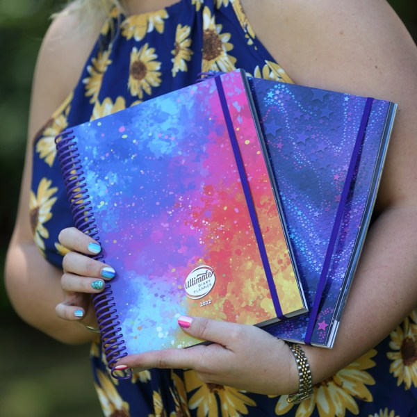 hands holding 2 Ultimate Diary Planners