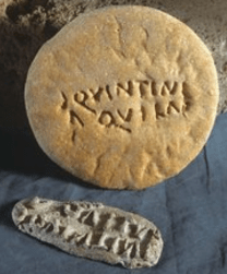 Loaf of bread with an ancient roman mark imprinted on it and the metal mark stamp.