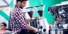 Homem faz moagem e torra do grão em microtorrefadora de café