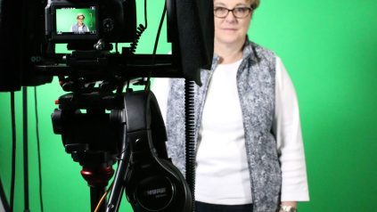 Faculty member in front of green screen