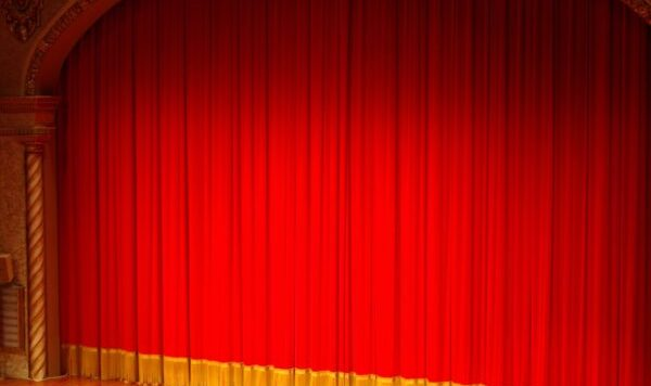 image of a brightly lit stage with red curtains