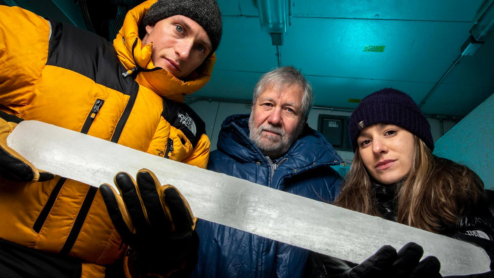 Three UMaine scientists hold an ice core