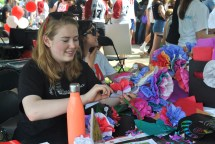 Students show guests how to make flowers out of tissue paper and pipe cleaners.
