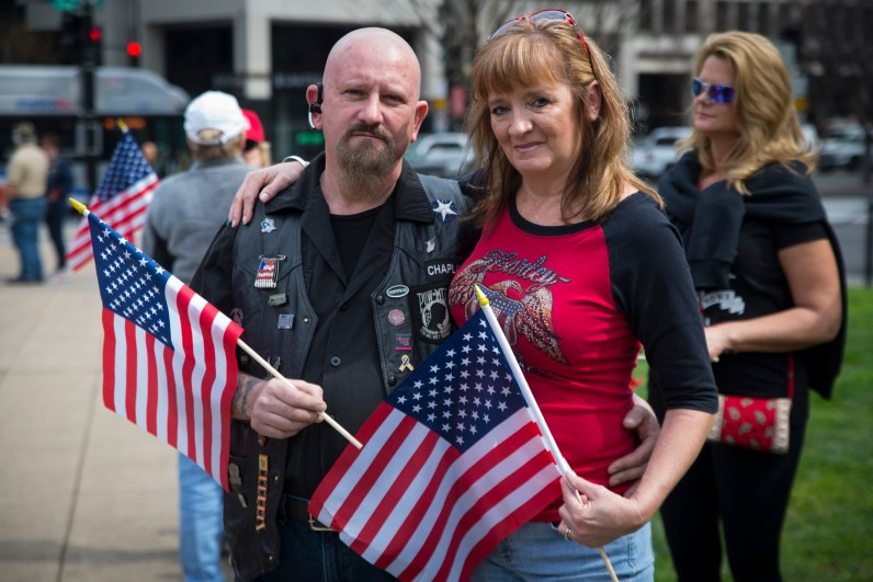 Bill and Tammy Blevins, who travelled here from Towson, Md., stand with American flags in Farragut square in Washington D.C. They came to the center of the district to have their voices heard at the Make America Great Again March held on Saturday, March 25, 2017. (Josh Loock/Bloc Photographer)