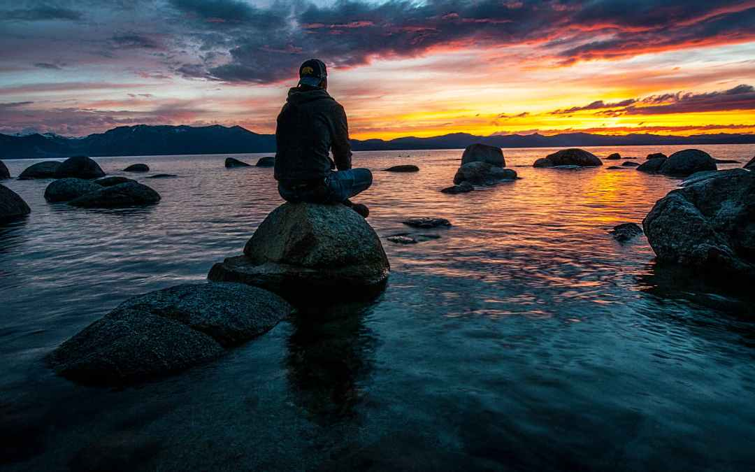 person sitting on rock on body of water