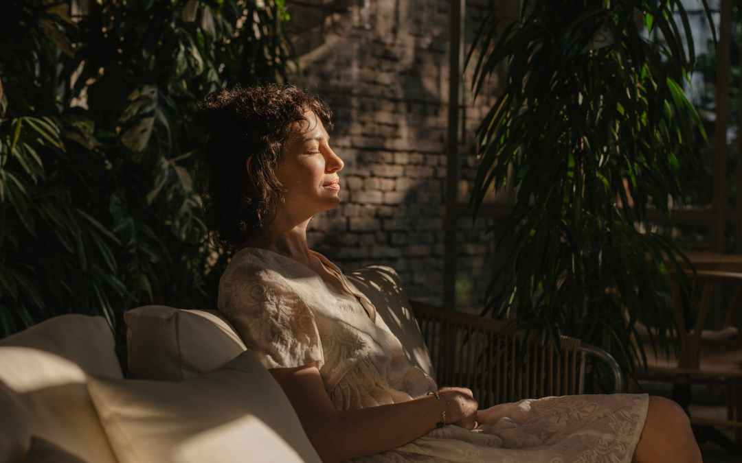 relaxed young woman sitting on couch with closed eyes in daylight