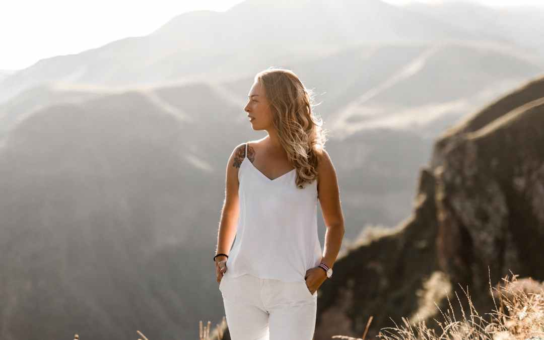 dreamy young woman admiring mountainous valley in sunlight