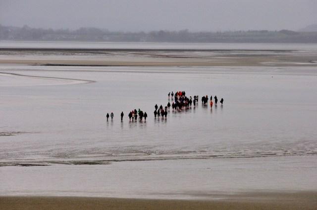 Os turistas fazem a travessia dos peregrinos no frio intenso da primavera da Normandia.