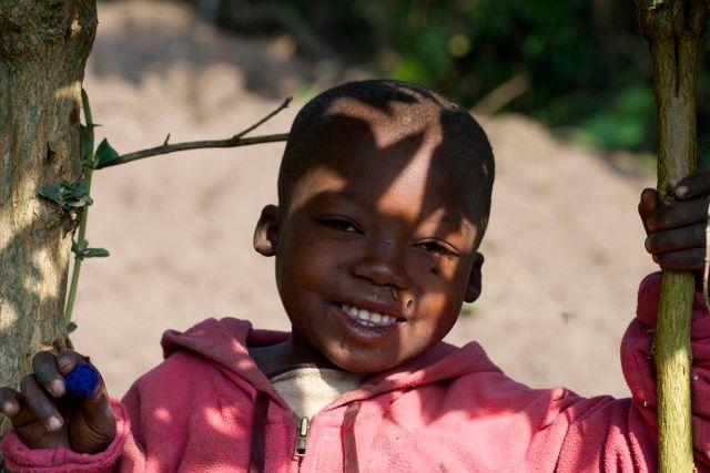 Criança na beira da estrada observando os carros de safari.
