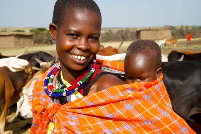 Jovem mulher Masai com o filho nas costas.