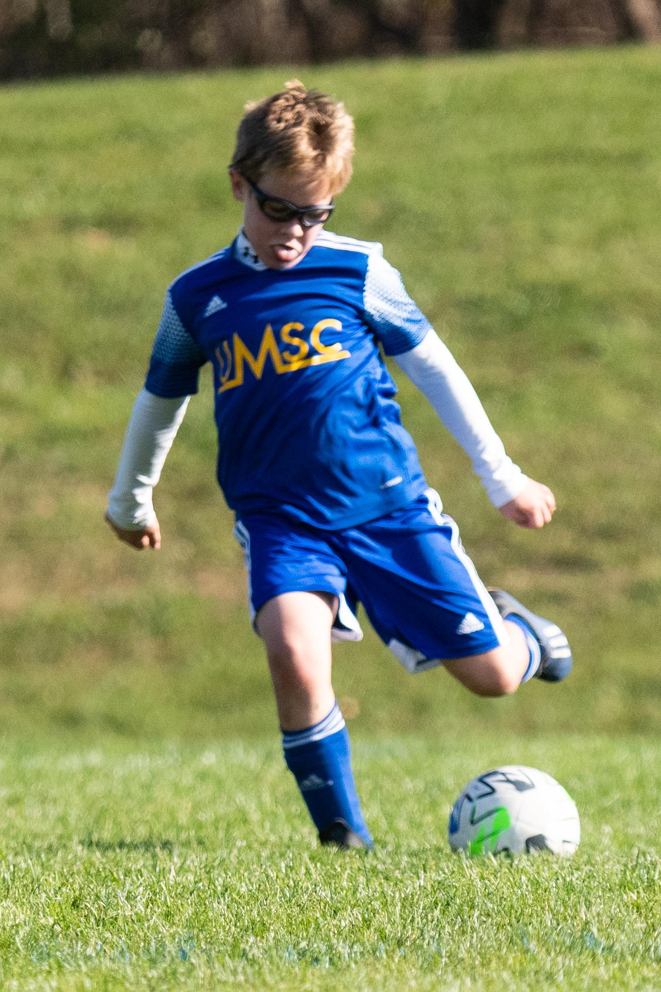 Boy shooting soccer ball