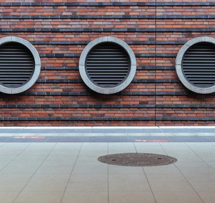 A photo of circular vents on a brick wall by Samuel Zeller on Unsplash