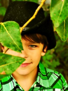 Young boy obscured by leaves - all natural health and wellness - un-pharma.com