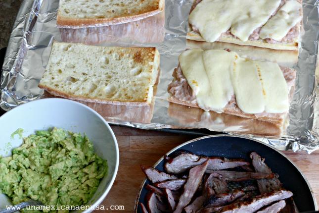 Pan con frijoles y queso Oaxaca derretido para preparar Pepitos, al lado aguacate machacado y carne asada en rebanadas.