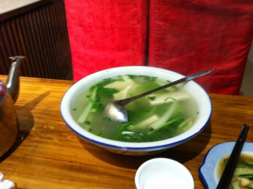 Huge bowl of tofu and green leafy plant